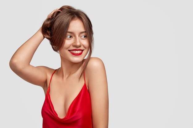 Joyeuse jeune femme brune posant contre le mur blanc