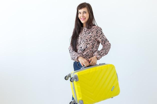 Joyeuse jeune femme brune souriante posant avec une valise jaune en attendant des vacances.