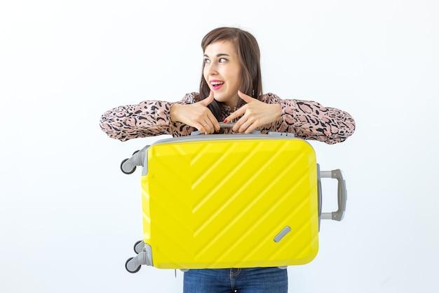 Joyeuse jeune femme brune souriante posant avec une valise jaune en attendant des vacances. le