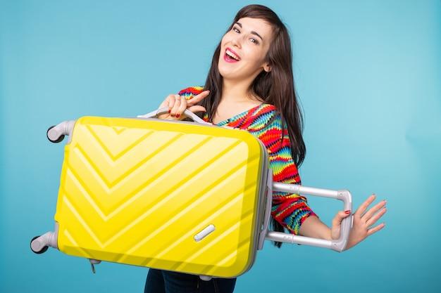 Joyeuse jeune femme brune souriante posant avec une valise jaune
