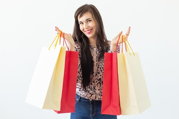 Joyeuse jeune femme brune tenant des sacs à provisions posant sur un fond blanc. concept de remises
