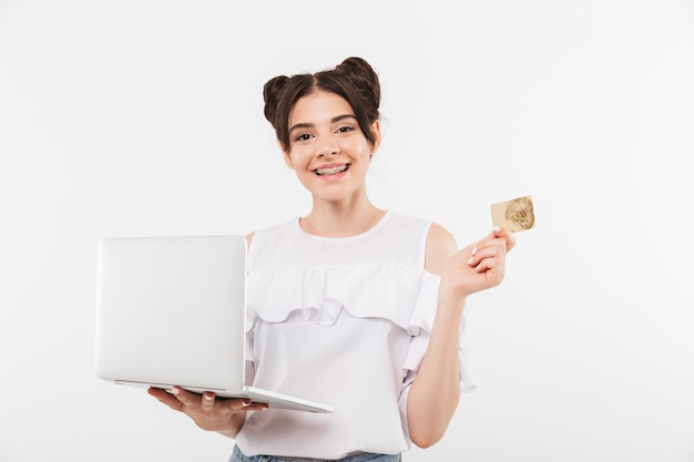 Joyeuse jeune femme avec une coiffure double chignons et un appareil dentaire tenant un ordinateur portable et une carte de crédit à deux mains, isolé sur blanc