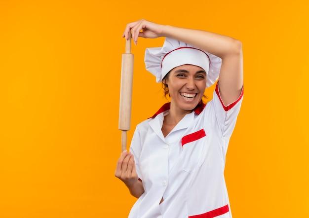Joyeuse jeune femme cuisinier portant l'uniforme de chef tenant un rouleau à pâtisserie sur un mur jaune isolé avec copie espace