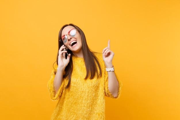 Joyeuse jeune femme dans des lunettes de coeur pointant l'index vers le haut en parlant au téléphone portable menant une conversation agréable isolée sur fond jaune. les gens émotion sincère style de vie. espace publicitaire.