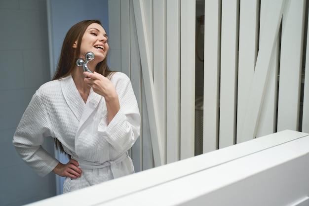 Joyeuse jeune femme dans un peignoir gaufré massant son cou devant le miroir