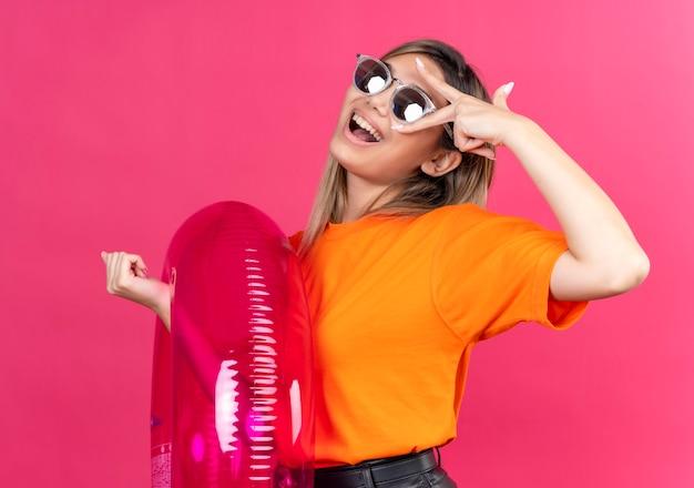 Une joyeuse jeune femme dans un t-shirt orange portant des lunettes de soleil souriant et regardant tout en tenant un anneau gonflable rose sur un mur rose