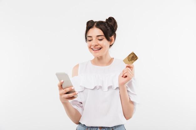 Joyeuse jeune femme avec double chignon coiffure et appareil dentaire à l'aide de smartphone et carte de crédit pour faire du shopping en ligne, isolé sur blanc