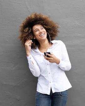 Joyeuse jeune femme avec écouteurs et téléphone intelligent