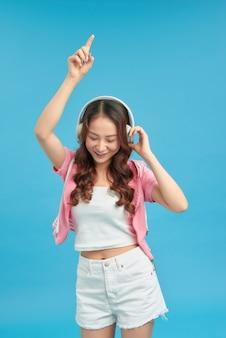 Joyeuse jeune femme élégante debout isolée sur fond bleu, écoutant de la musique avec des écouteurs, dansant