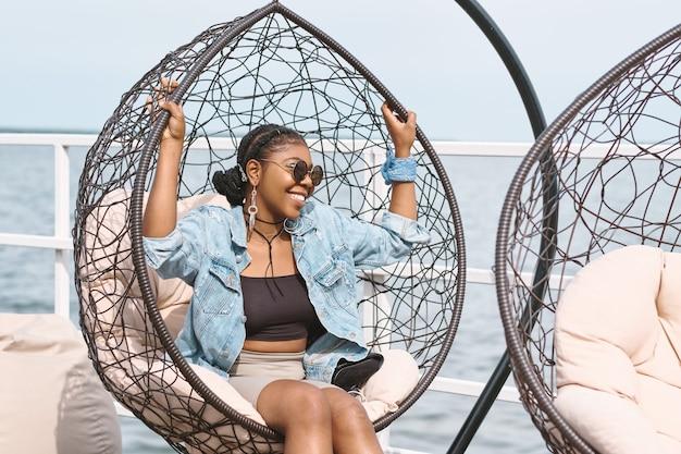 Joyeuse jeune femme élégante en veste en jean, lunettes de soleil et longues boucles d'oreilles assise dans un fauteuil suspendu à une fête d'anniversaire en plein air