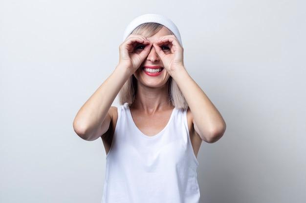 Joyeuse jeune femme faisant des jumelles en forme avec les doigts sur fond clair.