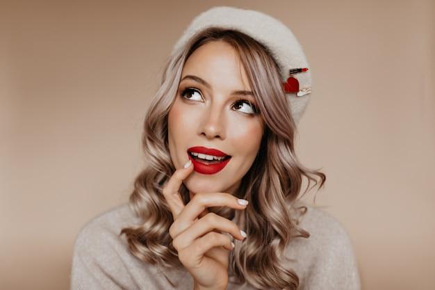 Joyeuse jeune femme glamour pense à quelque chose avec sourire
