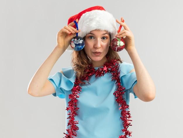 Joyeuse jeune femme en haut bleu et bonnet de noel avec guirlandes autour du cou tenant des boules de noël souriant confiant
