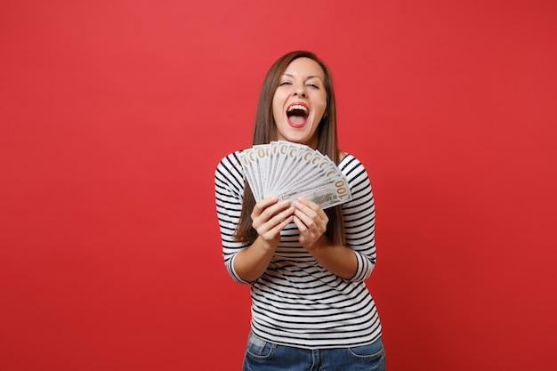 Joyeuse jeune femme heureuse gardant la bouche grande ouverte, tenant beaucoup de dollars, argent comptant isolé sur fond de mur rouge vif. les gens émotions sincères, concept de style de vie. maquette de l'espace de copie.