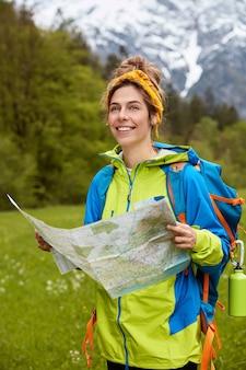 Joyeuse jeune femme heureuse habillée casully, lit la carte, trouve l'emplacement nécessaire, considère l'itinéraire
