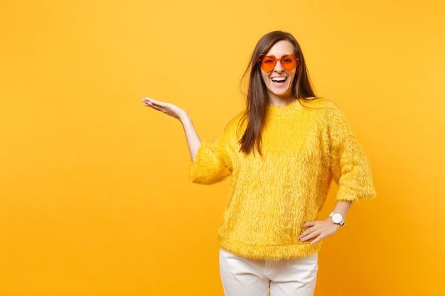 Joyeuse jeune femme heureuse en pull de fourrure et lunettes orange coeur pointant la main de côté sur l'espace de copie isolé sur fond jaune vif. les gens émotions sincères, concept de style de vie. espace publicitaire.