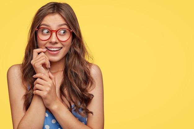 Joyeuse jeune femme avec des lunettes posant contre le mur jaune