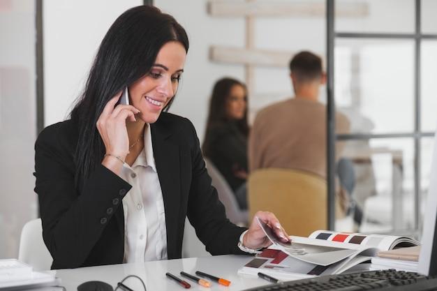 Joyeuse jeune femme avec un magazine et un téléphone