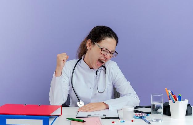 Joyeuse jeune femme médecin portant une robe médicale et un stéthoscope assis au bureau avec des outils médicaux faisant oui geste avec les yeux fermés isolés