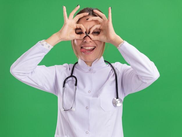Joyeuse jeune femme médecin portant une robe médicale avec stéthoscope montrant un geste de regard isolé sur un mur vert