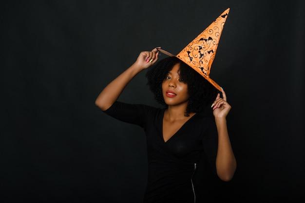 Joyeuse jeune femme noire avec coupe de cheveux afro portant un chapeau d'halloween