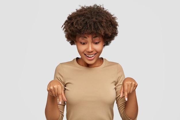 Joyeuse jeune femme noire pointe vers le bas