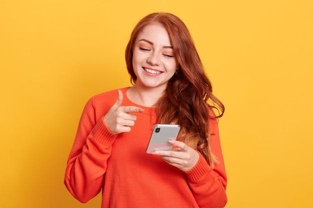 Joyeuse jeune femme pointant sur l'écran du téléphone intelligent dans la main