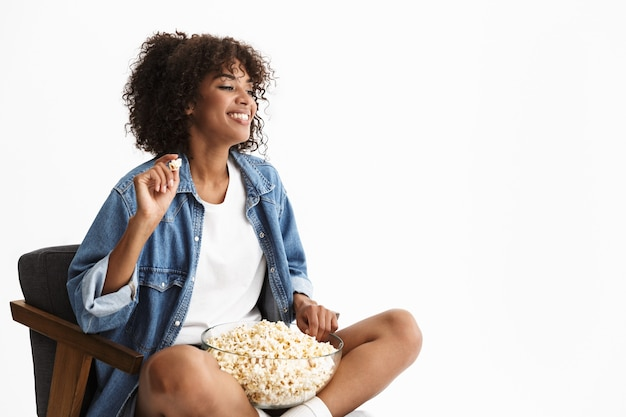 Joyeuse jeune femme portant des vêtements en denim décontractés, assise sur une chaise isolée sur un mur blanc, mangeant du pop-corn en regardant un film