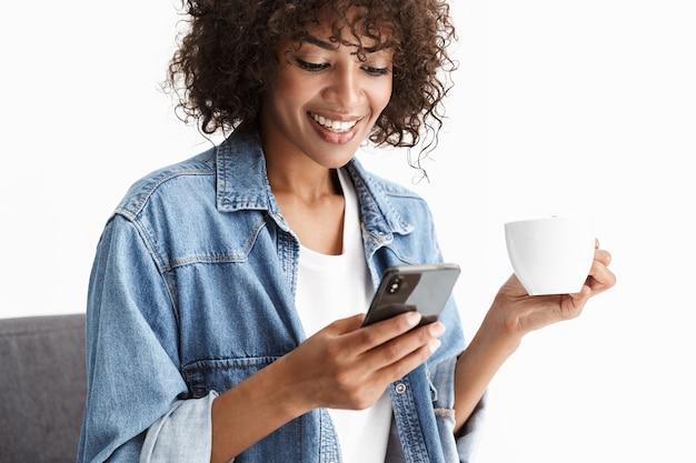Joyeuse jeune femme portant des vêtements en denim décontractés, assise sur une chaise isolée sur un mur blanc, tenant une tasse de café, utilisant un téléphone portable