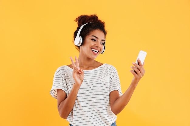 Joyeuse jeune femme positive dans les écouteurs à l'aide de téléphone isolé