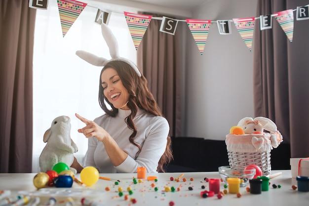 Joyeuse jeune femme positive se prépare pour pâques seule. elle est assise à table dans la chambre et joue avec un lapin blanc. peinture de décoration et bonbons colorés sur table. femme porte des oreilles festives.