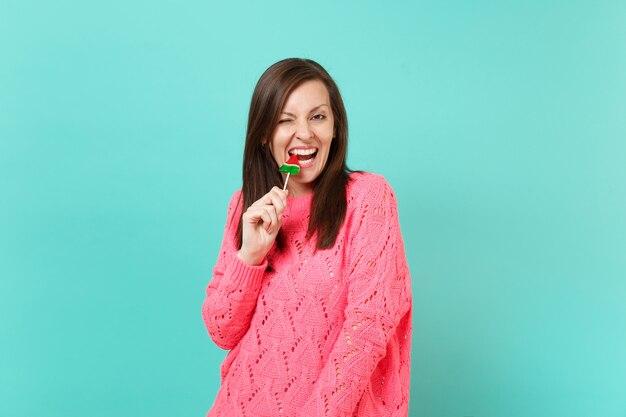 Joyeuse jeune femme en pull rose tricoté clignotant tenir dans la main une sucette de pastèque mordante isolée sur fond de mur bleu turquoise, portrait en studio. concept de mode de vie des gens. maquette de l'espace de copie.