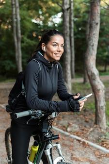 Joyeuse jeune femme de remise en forme à cheval sur un vélo dans le parc, écouter de la musique avec des écouteurs, tenant un téléphone mobile