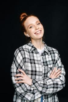 Joyeuse jeune femme rousse portant des écouteurs sans fil regardant la caméra avec les mains croisées