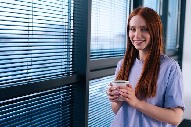 Joyeuse jeune femme rousse tenant une tasse avec du café au bureau à domicile debout près de la fenêtre