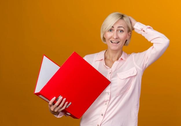 Joyeuse jeune femme slave blonde tenant le dossier et mettre la main derrière la tête isolée sur le mur orange