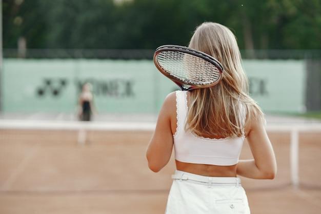 Joyeuse jeune femme en t-shirt. femme tenant une raquette de tennis et une balle.