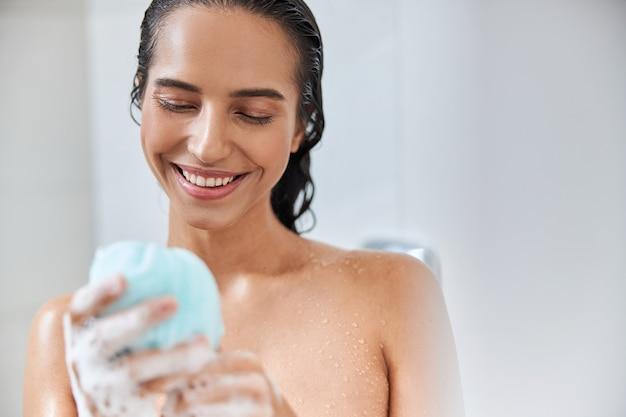Joyeuse jeune femme tenant une éponge de bain en luffa