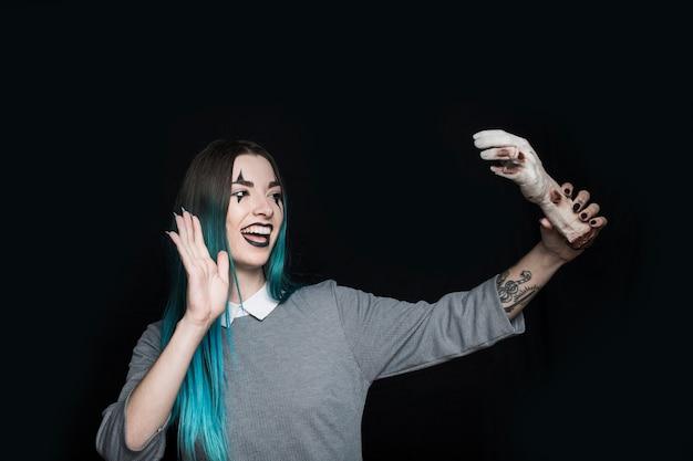 Joyeuse jeune femme tenant la main de morts-vivants