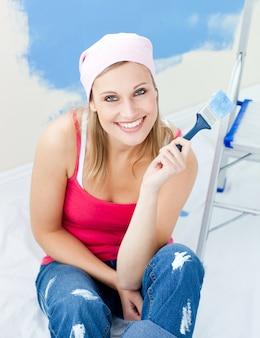 Joyeuse jeune femme tenant un pinceau souriant à la caméra