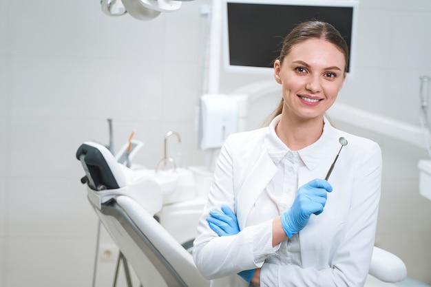 Joyeuse jeune femme en uniforme médical et gants stériles se tient dans un bureau moderne et tient un miroir dentaire.