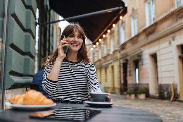 Joyeuse jeune femme en vêtements décontractés savourant un café frais et parlant au téléphone portable