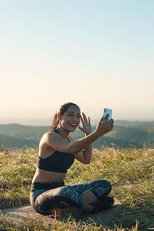 Une joyeuse jeune femme en vêtements de sport ayant un chat vidéo à l'extérieur, souriant et agitant
