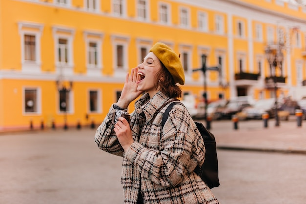 Joyeuse jeune femme voyageur appelle joyeusement quelqu'un et prend des photos sur son appareil photo rétro