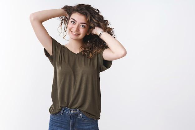 Joyeuse jeune fille arménienne insouciante jouant au peigne à cheveux bouclés, se tenant la main derrière le sourire faisant joyeusement une coiffure près du miroir, debout avec désinvolture sur fond blanc portant un jean t-shirt olive