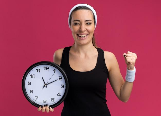Joyeuse jeune fille assez sportive portant un bandeau et des bracelets tenant une horloge faisant un geste fort isolé sur un mur cramoisi