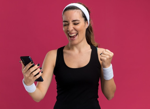 Joyeuse jeune fille assez sportive portant un bandeau et des bracelets tenant et regardant un téléphone portable faisant un geste oui