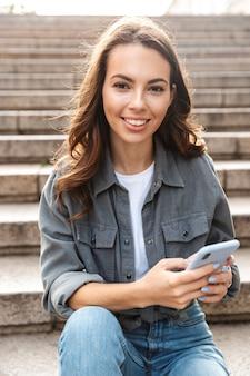 Joyeuse jeune fille assise dans les escaliers à l'extérieur, à l'aide d'un téléphone portable