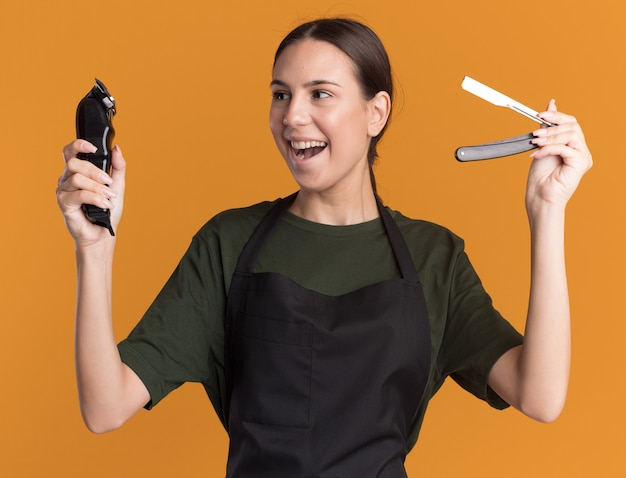 Joyeuse jeune fille de barbier brune en uniforme tient une tondeuse à cheveux et un rasoir droit isolé sur un mur orange avec espace de copie