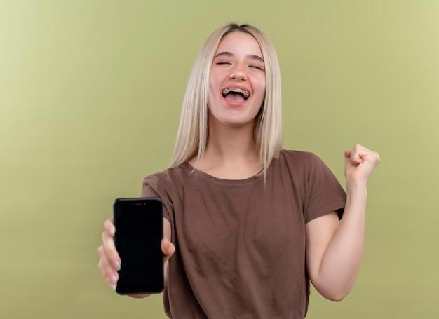 Joyeuse jeune fille blonde dans un appareil dentaire qui s'étend de téléphone mobile avec le poing levé et les yeux fermés sur un espace vert isolé